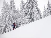 L'homme est dans les montagnes en hiver photos stock