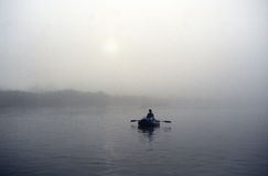 L'homme est dans un bateau photo stock