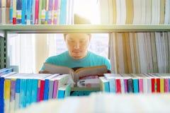 L'homme est des livres de lecture dans la bibliothèque Images libres de droits