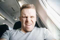 L'homme est fâché dans l'avion avant le départ Mécontentement en ce qui concerne le service, mangeant la mouche images stock