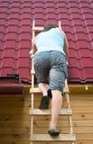 L'homme est monté les escaliers pour vérifier le toit de la maison après l'ouragan Images libres de droits