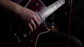L'homme est reposant et jouant la guitare dans une chambre noire Fin vers le haut 4K clips vidéos