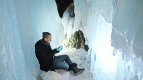 L'homme est se reposent sur l'Internet dans le comprimé dans une caverne de glace Autour de la belle grotte mystérieuse de glace  Photographie stock