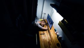 L'homme est tombé endormi à l'ordinateur, a fatigué du travail ou de l'étude images stock