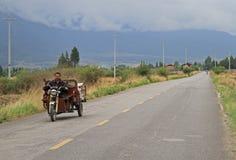 L'homme est tricycle de moteur d'entraînement sur la route presque Photo stock