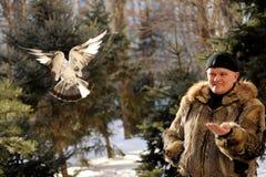 L'homme est venu au parc pendant l'hiver pour alimenter des titmouses et des pigeons images libres de droits