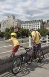 L'homme et l'enfant avec des bicyclettes Waterloo jettent un pont sur Londres R-U Photographie stock libre de droits