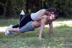 L'homme et la femme apprécient tout en s'exerçant ensemble en parc Image stock