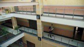 L'homme et la femme avec des documents se réunissent sur le deuxième étage du centre d'affaires clips vidéos