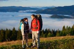 L'homme et la femme avec des sacs à dos regardent l'un l'autre dans les rayons du coucher du soleil contre des montagnes Photographie stock
