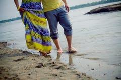 L'homme et la femme couplent la position sur la plage près de l'eau Photo libre de droits