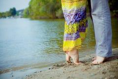 L'homme et la femme couplent la position sur la plage près de l'eau Photographie stock