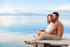 L'homme et la femme couplent se reposer sur une jetée sous un ciel nuageux bleu Photos libres de droits