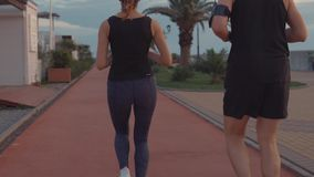 L'homme et la femme courent au-dessus du chemin dehors, vue en gros plan sur des jambes du dos banque de vidéos