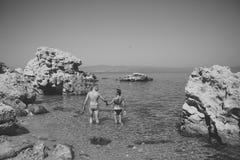 L'homme et la femme dans le bikini se tient en mer entre le récif le jour ensoleillé Le couple dans l'amour se tient dans l'eau p Photos stock