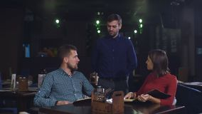 L'homme et la femme dans le serveur de restaurant apportent la carte et la nourriture d'ordre