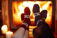 L'homme et la femme dans les chaussettes chaudes s'approchent de la cheminée Photographie stock