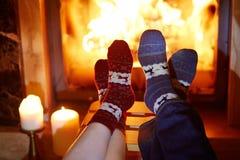 L'homme et la femme dans les chaussettes chaudes s'approchent de la cheminée Images stock