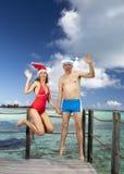 L'homme et la femme dans les sauts de chapeau de Santa-Klaus de nouvelle année sur le fond de la mer Images libres de droits