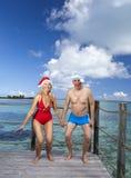 L'homme et la femme dans les sauts de chapeau de Santa-Klaus de nouvelle année sur le fond de la mer Photographie stock