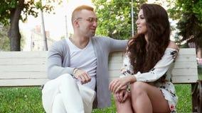 L'homme et la femme la date en parc de ville, flirtent au banc sur le coucher du soleil banque de vidéos