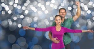 L'homme et la femme de sourire avec des bras ont augmenté au-dessus du bokeh Photographie stock libre de droits
