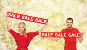L'homme et la femme de sourire avec la vente rouge signe Photos stock