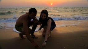 L'homme et la femme dessinent sur le coeur de sable banque de vidéos