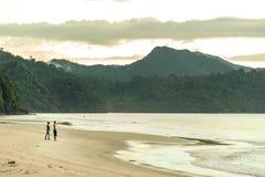 L'homme et la femme donnent sur les rivages de l'océan image stock