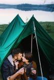L'homme et la femme en nature dans une tente boivent du thé chaud Photos stock