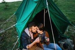 L'homme et la femme en nature dans une tente boivent du thé chaud Image stock