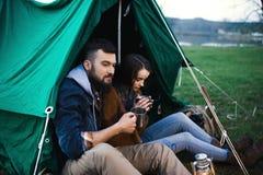 L'homme et la femme en nature dans une tente boivent du thé chaud Photo libre de droits