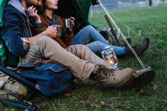 L'homme et la femme en nature dans une tente boivent du thé chaud Image libre de droits