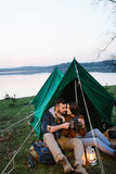 L'homme et la femme en nature dans une tente boivent du thé chaud Photo stock