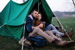 L'homme et la femme en nature dans une tente boivent du thé chaud Photographie stock libre de droits