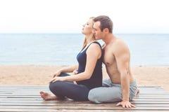 L'homme et la femme enceinte font le yoga sur la plage Images stock