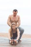 L'homme et la femme enceinte font le yoga sur la plage Photographie stock libre de droits