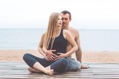 L'homme et la femme enceinte font le yoga sur la plage Photographie stock