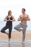 L'homme et la femme enceinte font le yoga sur la plage Photos stock
