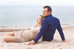 L'homme et la femme enceinte se reposent sur la plage Photos stock