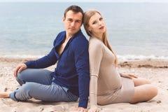 L'homme et la femme enceinte se reposent sur la plage Photographie stock libre de droits