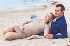 L'homme et la femme enceinte se reposent sur la plage Photo libre de droits