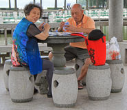 L'homme et la femme jouent des cartes extérieures à Wuhan, Chine photo stock
