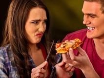 L'homme et la femme mangent de la pizza de tranche avec le couteau et la fourchette Photographie stock
