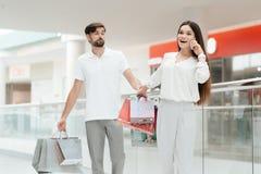 L'homme et la femme marchent à un autre magasin dans le centre commercial La femme parle au téléphone photo stock