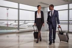 L'homme et la femme optimistes portent des valises à l'aéroport Photos stock