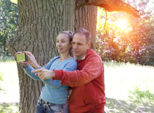 L'homme et la femme près d'un chêne dans le jour d'été montrent au côté et photographient au téléphone Photographie stock