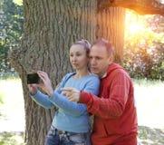L'homme et la femme près d'un chêne dans le jour d'été montrent au côté et photographient au téléphone Image stock