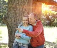 L'homme et la femme près d'un chêne dans le jour d'été quelque chose ont été vus de côté et ont regardé avec un sourire Image libre de droits
