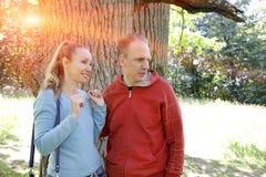 L'homme et la femme près d'un chêne dans le jour d'été quelque chose ont été vus de côté et ont regardé avec un sourire Photographie stock libre de droits